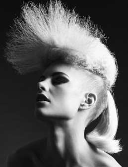 A contrasty black and white photograph of a model with striking blond hair. This photo was taken for Yoshiko Hairdressing by photographer Peter Rosetzky
